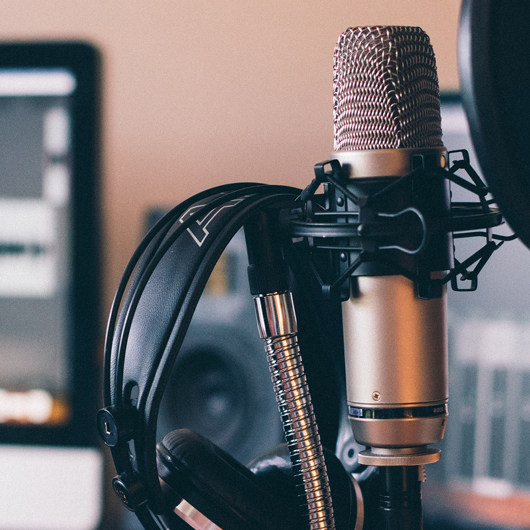 Image of a podcast microphone and headphones