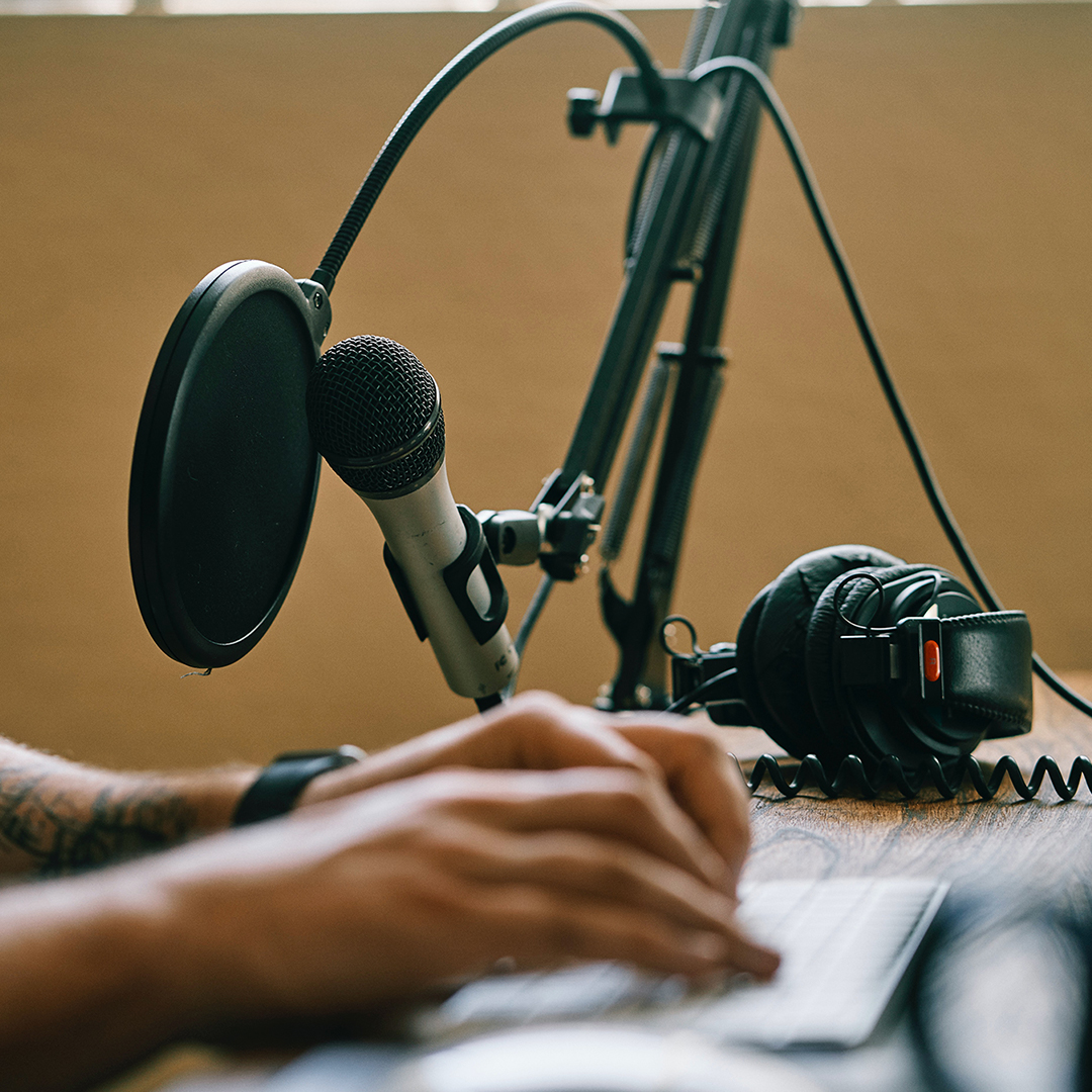 Image of a podcaster by his microphone typing on a computer