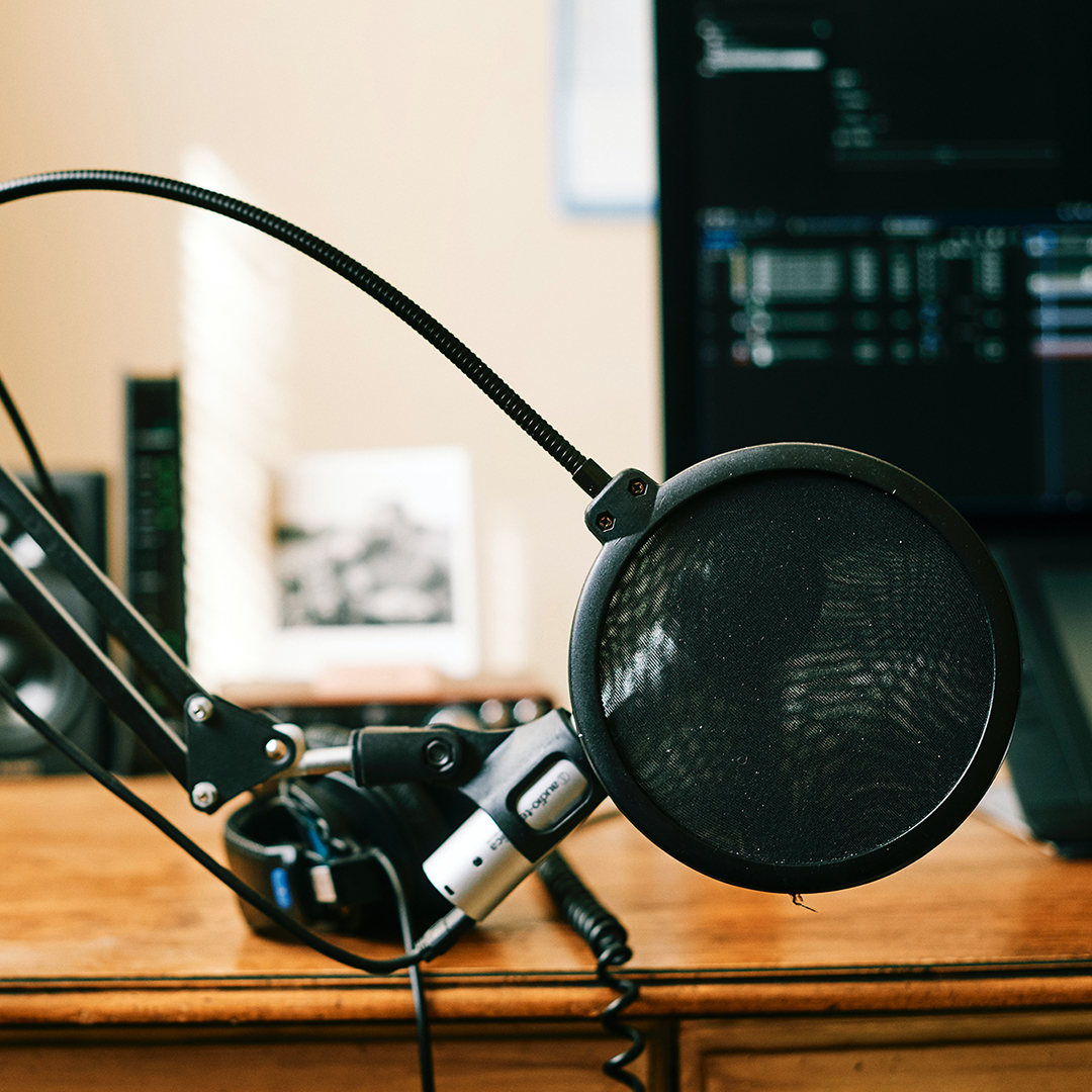 Image of a podcasting setup with desk, mic, and editing software