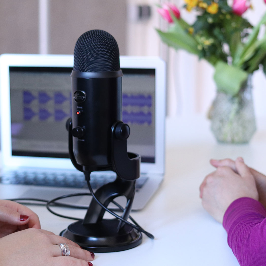 Image of two female entrepreneurs recording a podcast in their living room