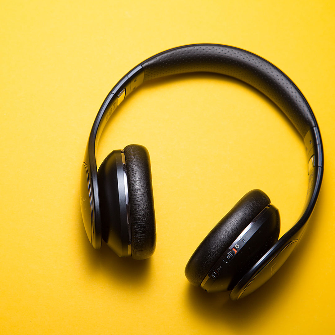 An image of a woman wearing headphones listening to a podcast